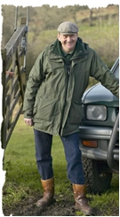 Les Davies MBE, FRGS standing next to 4 wheel drive in gateway wearing countryside clothes and cap